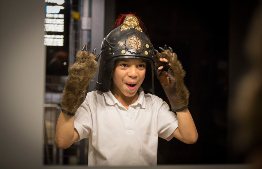 Boy dressing up with bear paws and military Roman helmet