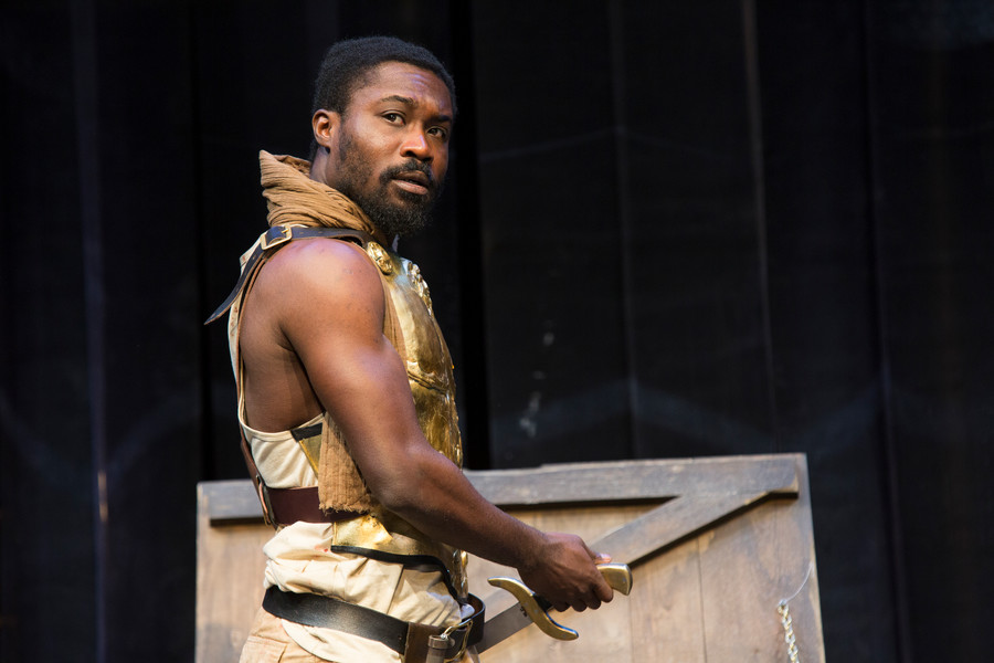 An actor in gold armour playing a warrior