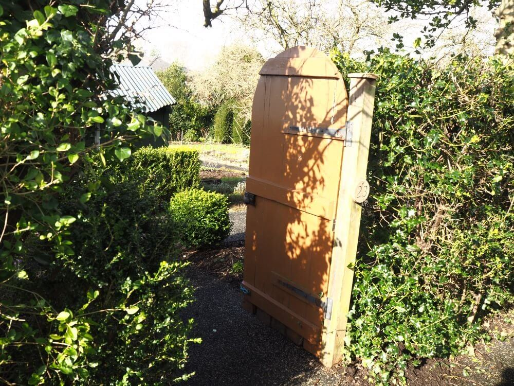 A gate in the hedgerow leads to a garden plot
