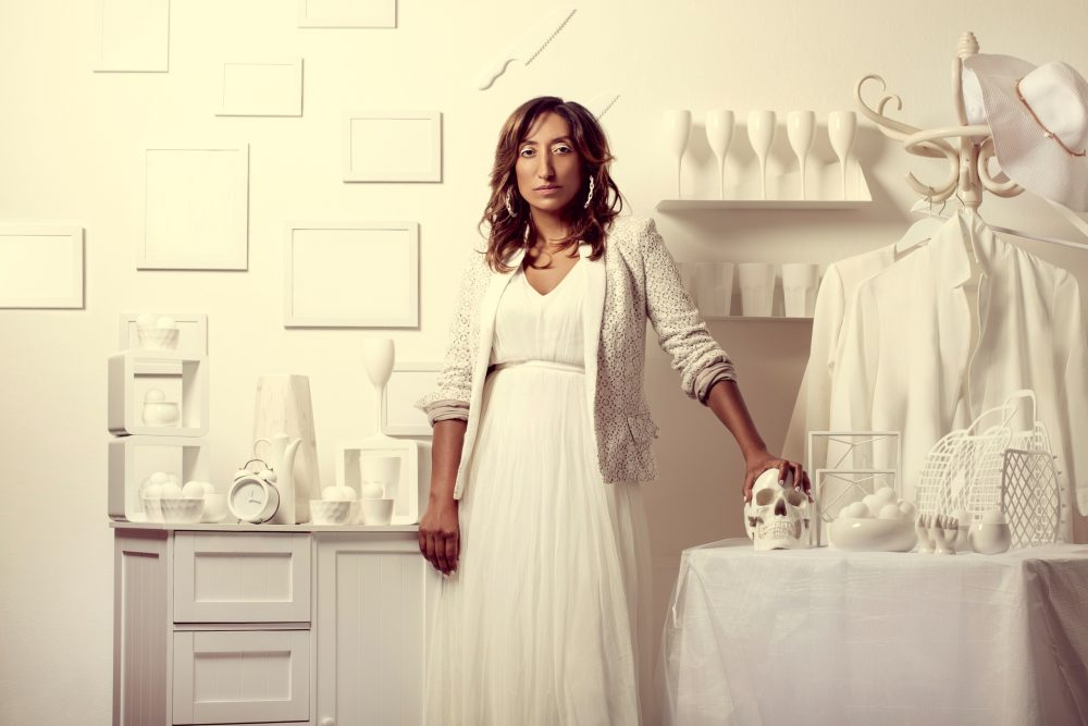 Comedian Shazia Mirza dressed in white in a white room