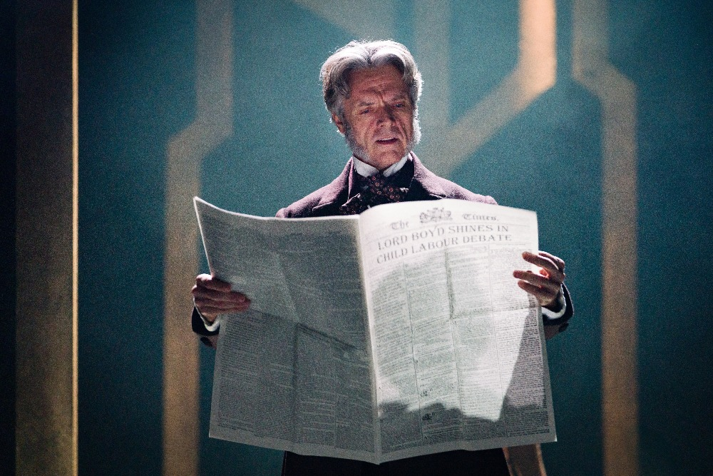 Actor in Victorian costume reading a newspaper