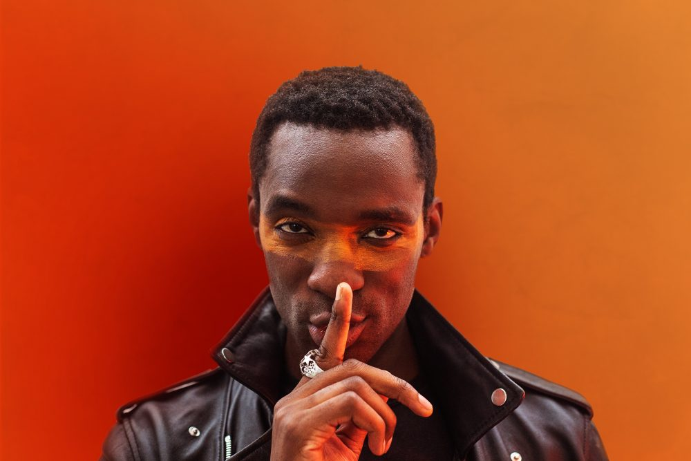 Man in leather jacket standing against an orange background