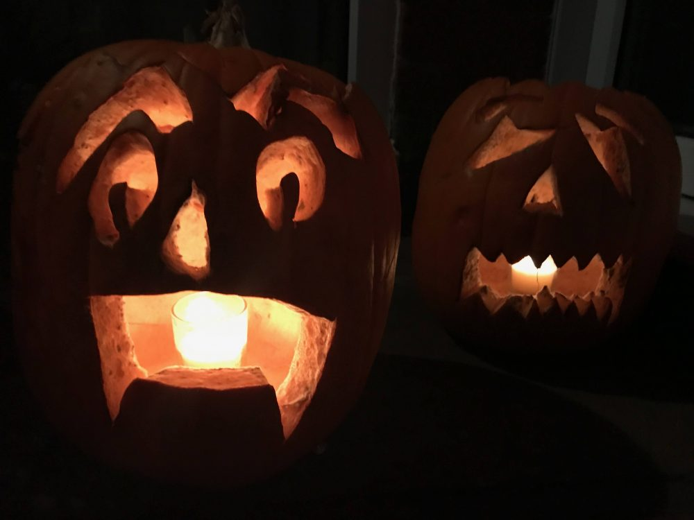 carved pumpkins lit by candles