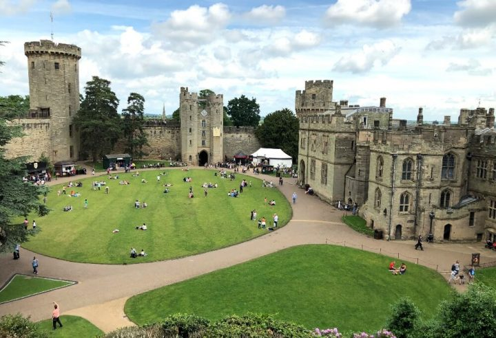 Looking from above within the walls of Warwick Castle with its turrets and green spaces