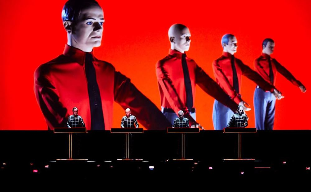 Red screen with four dummies and four men on keyboards